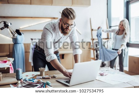 Couple of fashion designers are working in workshop. Attractive young woman and stylish bearded man are in process of creating new clothes collection. Royalty-Free Stock Photo #1027534795