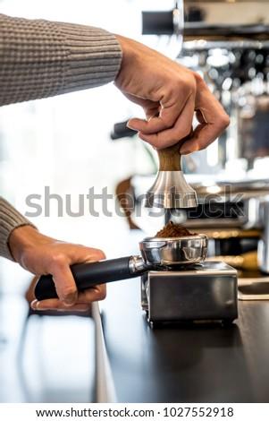 Barista presses ground coffee using tamper #1027552918