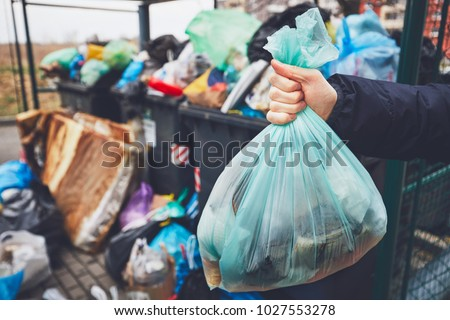 Hand with garbage against full trash cans with rubbish bags overflowing onto the pavement. Royalty-Free Stock Photo #1027553278