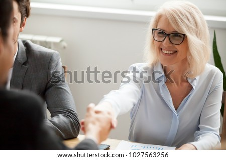 Smiling attractive mature businesswoman handshaking businessman at meeting negotiation, happy hr senior executive woman shaking hand welcoming new hire partner, making deal satisfied with good result Royalty-Free Stock Photo #1027563256