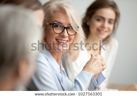 Smiling aged businesswoman in glasses looking at colleague at team meeting, happy attentive female team leader listening to new project idea, coach mentor teacher excited by interesting discussion Royalty-Free Stock Photo #1027563301