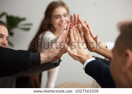 Motivated successful business team giving high five, happy young students employees group join hands with senior teacher mentor, team building unity concept, help support in teamwork, close up view #1027563358