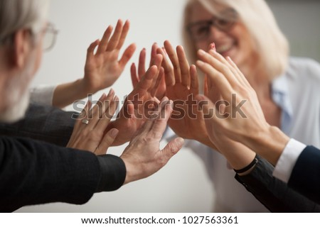 Hands of diverse business people giving high five, smiling team members, teachers and students promising help unity in goal achievement, coaching support in mentoring teamwork concept, close up view #1027563361
