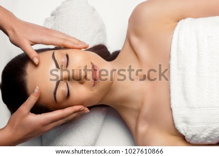 Portrait of Young Beautiful Woman in Spa Salon.Spa Body Massage Treatment and Skincare.Leisure. Face Massage.Facial treatment. Cosmetology #1027610866