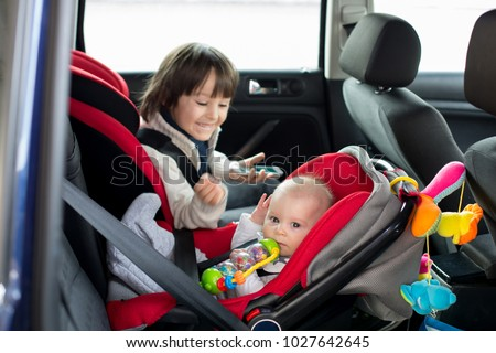 Little baby boy and his older brother, traveling in car seats, going on a holiday, preschool boy playing with mobile phone #1027642645