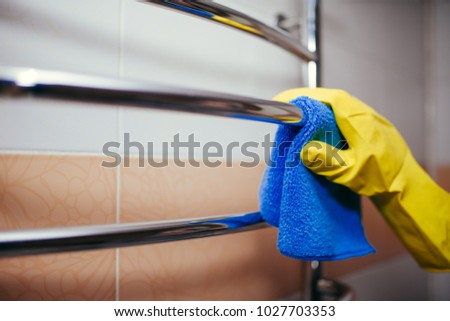 Commercial cleaning. Employee hand in rubber protective glove with micro fiber cloth washing a ceramic tiles from dust in the bathroom. #1027703353