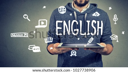 Learning rnglish with new technology concept. Young man holding a tablet computer Royalty-Free Stock Photo #1027738906