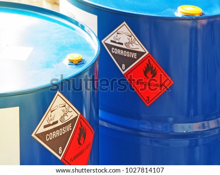 the close-up shot of blue color hazardous dangerous chemical barrels ,have warning labels of corrosive & flammable liquid in daylight on daytime. #1027814107