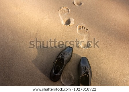 Work Life Balance Concept, Businessman take off his Working Oxford Shoes and leave it on the Sand Beach for Walk into the Sea on Sunny Day. Top View #1027818922