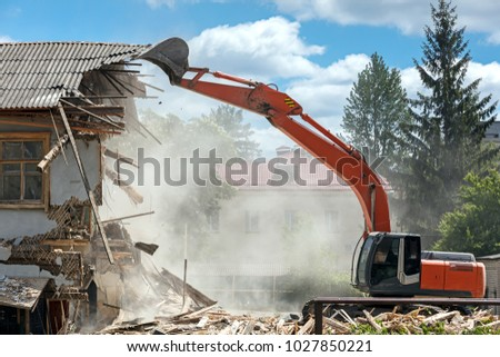 industrial excavator working at the demolition of an old residential building Royalty-Free Stock Photo #1027850221
