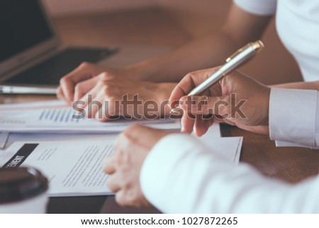 Businessman writing signed agreements on official documents to the company's profits. Which is filled with documents and concepts for the cooperation of its partners. #1027872265