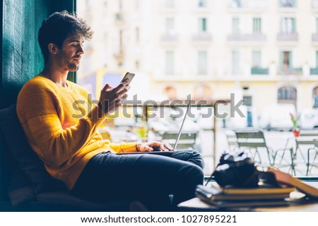 Side view of male blogger browsing profile in networks on smartphone via 4G internet connection resting in stylish coffee shop with modern laptop computer.Young man chatting online on mobile phone #1027895221