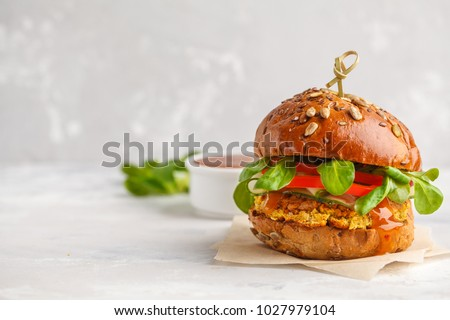 Vegan lentils burger with vegetables and curry sauce. Light background, copy space. Vegan food concept. #1027979104