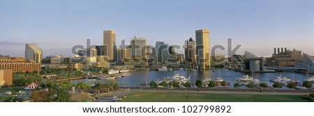 This is the skyline of Baltimore in daylight showing the inner harbor and city lights. There are boats moored in the harbor