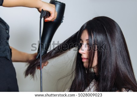 Professional hair stylist with hairdryer and comb working at customer's hair. Horizontally framed shot. #1028009023