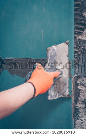 The worker leveling the wall for facing works, preparing for the installation of tiles #1028016910