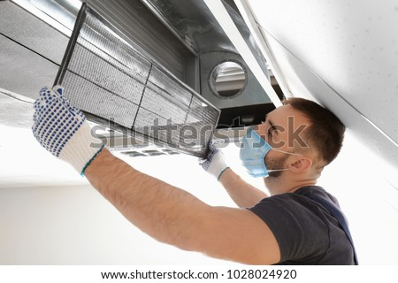 Male technician cleaning industrial air conditioner indoors Royalty-Free Stock Photo #1028024920