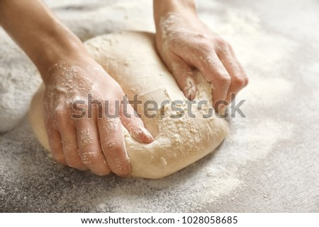 Woman kneading dough on table, closeup #1028058685