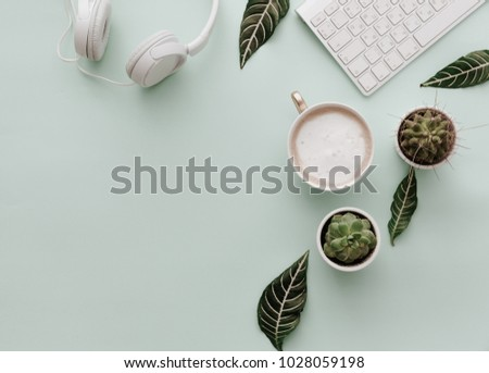 Neutral Minimalist Flat Lay Scene With coffee, keyboard, headphones and cactus #1028059198