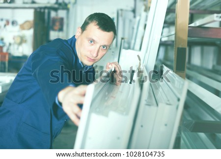 Serious production worker in coverall with different PVC windows and doors #1028104735