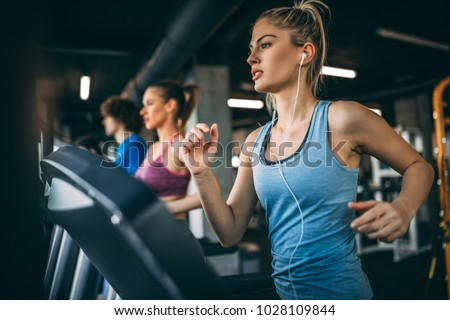 Young people running on a treadmill in health club. #1028109844