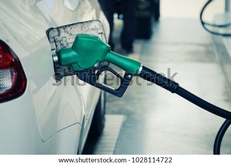 close up nozzle  fuel fill oil into car  tank at pump gas station, saving money and energy for transport, manage for success business concept, vintage tone #1028114722