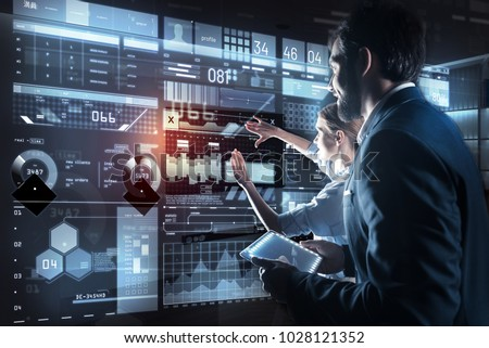 Best variant. Clever excited qualified programmers standing in front of a modern transparent screen and looking attentively at it while discussing their new amazing program #1028121352