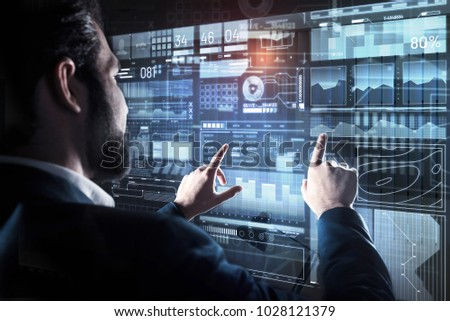 Comparison. Calm experienced bearded programmer touching the transparent screen with two fingers while comparing different information during his working day #1028121379