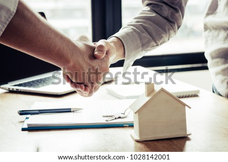 Successful agreement , estate,home buying contract concept, buyer shaking hand with bank empoyees after finishing signing contract in office  #1028142001