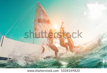 Happy crazy friends diving from sailing boat into the sea - Young people jumping inside ocean in summer vacation - Main focus on center man - Travel and fun concept - Fisheye lens distortion #1028169820