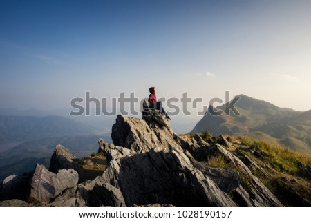 Women tourists sit at the top of the rock, Beautiful view point Sunset of travel place at Doi Pha Tang, Chiang Rai's Hidden Paradise,Thailand. #1028190157