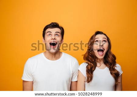 Ecstatic young man and woman in white t-shirts looking upward in excitement with open mouth, isolated over yellow background #1028248999