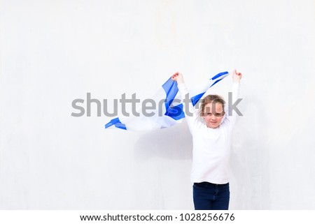 Little patriot jewish girl standing  and enjoying with the flag of Israel on white wall background.Memorial day-Yom Hazikaron, Patriotic holiday Independence day Israel - Yom Ha'atzmaut concept.  #1028256676