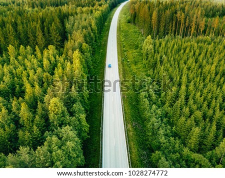 Aerial view from above of country road through the green summer forest in summer Finland. drone photography #1028274772