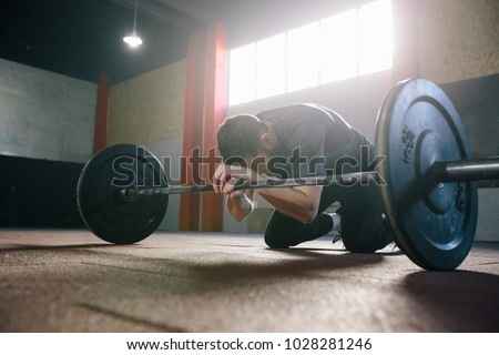 Athlete man with a beard exercising in a gym #1028281246