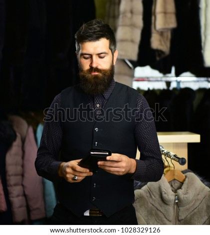 Man in black suit with calm face in front of fur shop. Macho with beard and mustache holds wallet with shopping mall on background, defocused. Guy looks at his wallet. Purchase and shopping concept. #1028329126