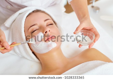 Woman in mask on face in spa beauty salon #1028333365