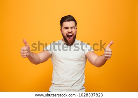 Portrait of an excited bearded man showing thumbs up isolated over yellow background #1028337823