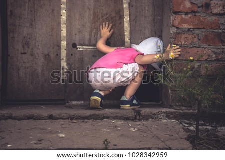Curious child lookinginto dark hole in barn door in countryside shed concept curiosity Royalty-Free Stock Photo #1028342959
