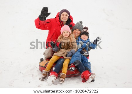Picture of happy parents with daughter and son sitting on tubing in winter