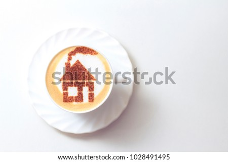coffee cappuccino in a white cup with a picture of a house made from cinnamon on milk foam
