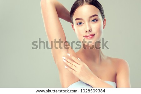 Young woman holding her arms up and showing underarms, armpit smooth clear skin .Girl showing clean armpit .Beauty portrait.Epilation and depilation of hair .  #1028509384