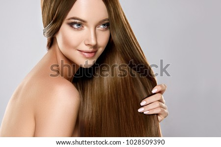 Beautiful model girl with shiny brown and straight long  hair . Keratin  straightening . Treatment, care and spa procedures. Smooth hairstyle  Royalty-Free Stock Photo #1028509390