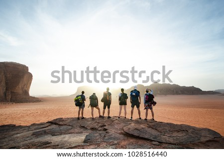 Tourist friends on a top of mountains in a desert. Sunset view. Nature. Tourist people enjoy a moment in a nature. Wadi rum national park - Jordan  #1028516440
