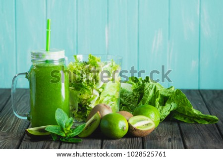 Blended green smoothie with ingredients on wooden table selective focus. Blue background. #1028525761