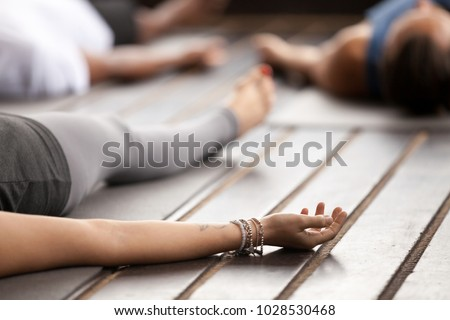 Group of young sporty people practicing yoga, lying in Corpse pose, Savasana exercise, working out, resting after practice, female hand with wrist bracelets close up, studio. Healthy lifestyle concept #1028530468