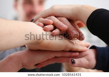 Group of people in suits crossed hands in pile for win #1028561431