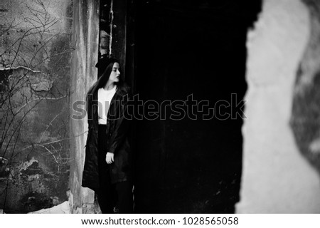 Fashionable long legs brunette model in long black cloak posed outdoor at winter day against old grunge wall. #1028565058
