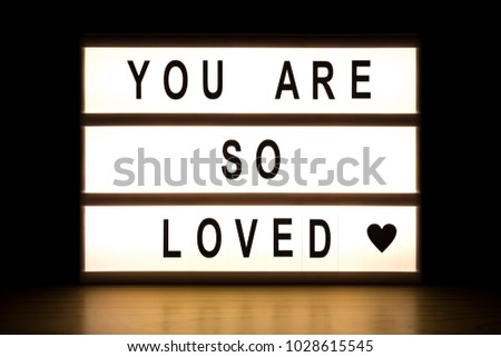 You are so loved light box sign board on wooden table.