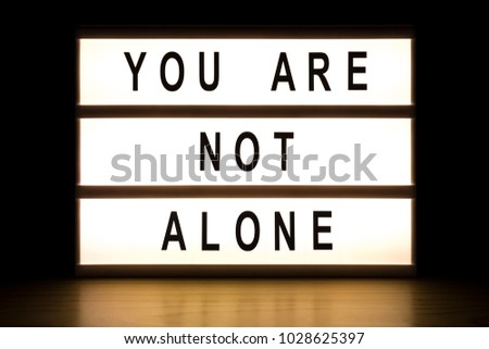 You are not alone light box sign board on wooden table.  #1028625397